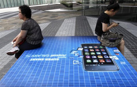 People holding their mobile phones sit on an advertisement of Samsung Electronics' Galaxy S smartphone outside the company's headquarters in