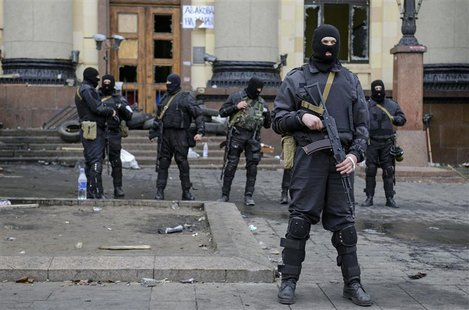 Armed men in masks, representing Ukrainian special forces, stand guard outside the regional administration building in Kharkiv, April 8, 201