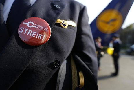 "A pilot of German airline Lufthansa, sports a buttons reading ""strike"" on his uniform as he takes part in a demonstration at Fraport airport"