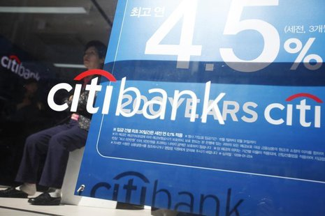 A woman sits next to an advertisement board for interest rates of savings deposits for Citibank in central Seoul October 11, 2012. REUTERS/K