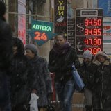 People pass by a board showing currency exchange rates in Moscow, February 11, 2014. REUTERS/Maxim Shemetov