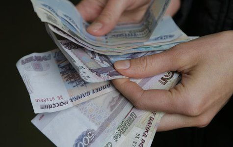 A vendor counts Russian rouble banknotes at a market in Moscow, March 3, 2014. REUTERS/Maxim Shemetov
