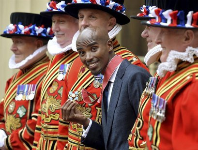 Britain's double Olympic champion Mo Farah poses with his Commander of the Order of the British Empire (CBE) medal, after being presented wi