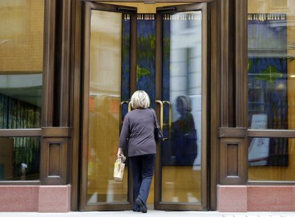A woman enters the offices of private equity firm APAX in London May 18, 2012. Apax Partners LLP has lost or terminated more than half of it