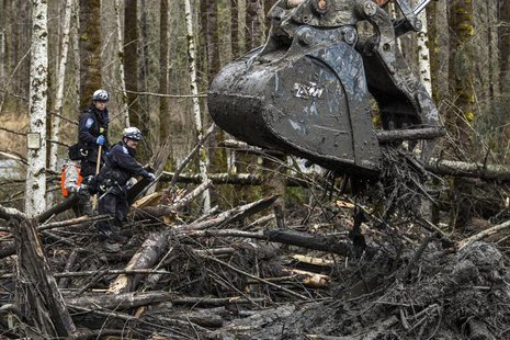Rescuers watch carefully as an excavator combs through the large debris pile left by a mudslide in Oso, Washington, April 4, 2014. REUTERS/M