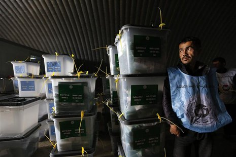 An Afghan election worker stands next to ballot boxes at a counting centre in Kabul April 6, 2014. REUTERS/Mohammad Ismail