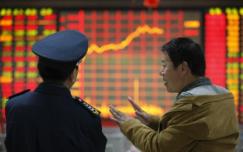 An investor (R) talks to a security guard in front of an electronic board showing stock information at a brokerage house in Huaibei, Anhui p