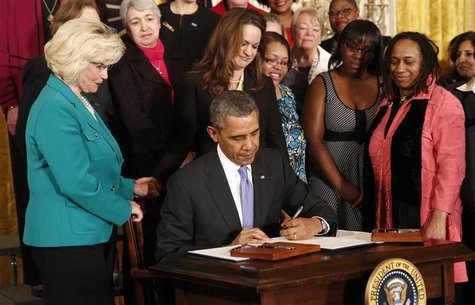 U.S. President Barack Obama signs two new executive actions aimed at increasing transparency about women's pay during an event at the White