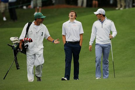 Britain's amateur Matthew Fitzpatrick (C) and Northern Ireland's Rory McIlroy (R) walk up the ninth fairway during a practice round ahead of