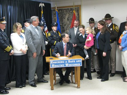 Gov. Scott Walker talking to Lillie Moe, who is Senator Julie Lassa's youngest daughter before signing part of the H.O.P.E. legislation.  Also pictured: members of the Stevens Point Police Department and Portage County Sheriff's Department, Rep. John Nygren, Mayor Andrew Halverson, Rep. Amy Sue Vruwink