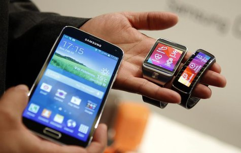 The new Samsung Galaxy S5 smartphone (L), Gear 2 smartwatch (C) and Gear Fit fitness band are displayed at the Mobile World Congress in Barc