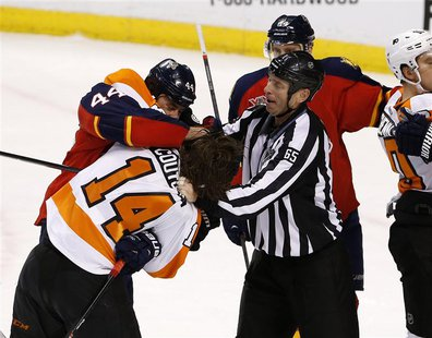 Apr 8, 2014; Sunrise, FL, USA; Linesman Pierre Racicot (65) tries to break up a fight between Florida Panthers defenseman Erik Gudbranson (4