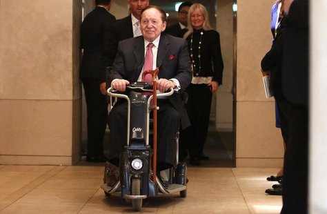 Las Vegas Sands Corp Chairman and Chief Executive Officer Sheldon Adelson rides his wheelchair after a news conference in Tokyo February 24,
