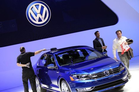 A worker dusts a Volkswagen Passat Blue Motion Concept as visitors look on during the North American International Auto Show in Detroit, Mic