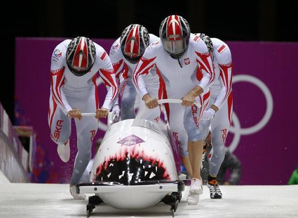 Poland's pilot Dawid Kupczyk (front R), Daniel Zalewski, Michal Kasperowicz and Pawel Mroz start a heat during the four-man bobsleigh event