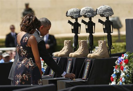 U.S. President Barack Obama places a challenge coin on a memorial as he and first lady Michelle Obama pay their respects for the dead soldie