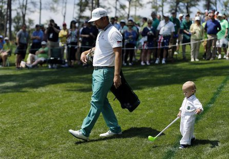 U.S. golfer Ryan Moore and his son Tucker (R) walk along the third hole during the Par 3 contest ahead of the Masters golf tournament at the