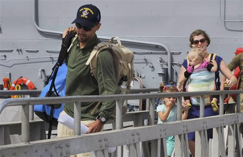 Eric and Charlotte Kaufman and their two daughters, 3-year-old Cora and 1-year-old Lyra, disembark the USS Vandegrift in San Diego April 9,