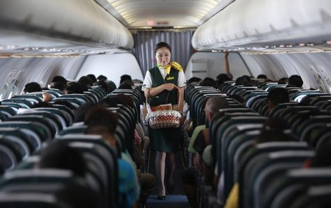 A Spring Airlines crew member sells food onboard an Airbus A320 aircraft near Shanghai July 6, 2012. REUTERS/Aly Song