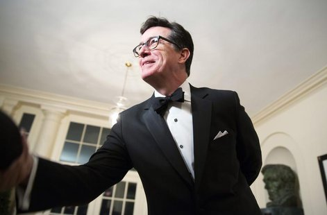 Comedian Stephen Colbert greets a reporter as he arrives for the State Dinner being held for French President Francois Hollande at the White
