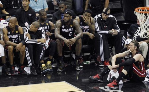 Miami Heat's LeBron James (6) sits with his teammates near the end of their loss to the San Antonio Spurs in Game 5 of their NBA Finals bask