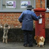 A dog walker posts a letter in a Royal Mail post box in Maybury near Woking in southern England March 25, 2014. REUTERS/Luke MacGregor