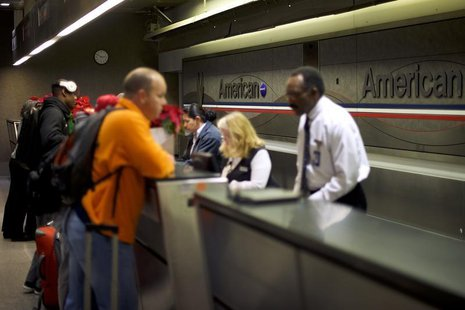 Employees check in travelers at the American Airlines check in counters at Philadelphia International Airport in Philadelphia, Pennsylvania