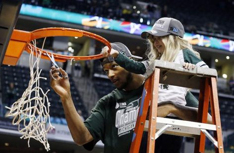 """Princess Lacey"" Holsworth and Adreian Payne cutting down the nets after Michigan State won the Big Ten Championship. (Photo : Reuters)"