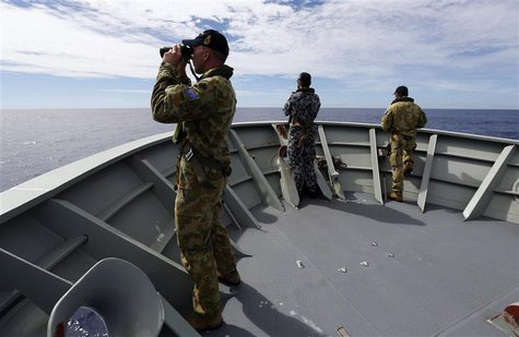 Gunner Richard Brown (L) of Transit Security Element looks through binoculars as he stands on lookout with other crew members aboard the Aus