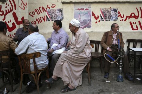 People sit at a cafe near posters of presidential candidate and former Egyptian army chief Field Marshal Abdel Fattah al-Sisi in central Cai