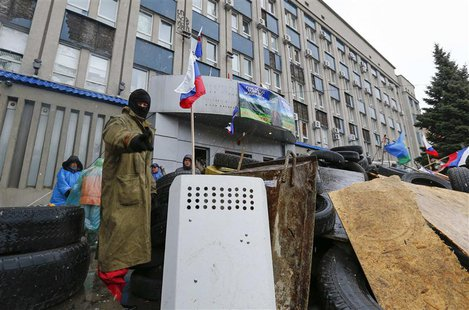 A pro-Russian protester gestures as he stands guard at a barricade in front of the seized office of the SBU state security service in Luhans