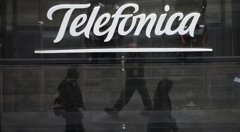 People are reflected as they walk past Spanish telecom group Telefonica's flagship store in central Madrid November 8, 2013. REUTERS/Sergio