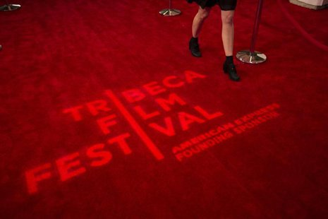 A woman walks past a logo displayed on a red carpet on the opening night of the Tribeca Film Festival in New York, April 17, 2013. REUTERS/L