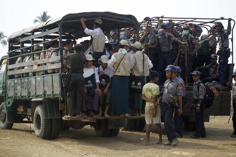 Volunteers and police board vehicles before proceeding to Rohingya refugee camps to collect data for the census in Sittwe March 31, 2014. RE