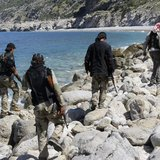 Rebel fighters walk with their weapons at the beach in Latakia province near the town of Kasab April 5, 2014. Picture taken April 5, 2014. R