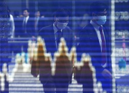 Men, wearing masks, are reflected on a screen displaying a graph showing movements of Shanghai B shares outside a brokerage in Tokyo April 9
