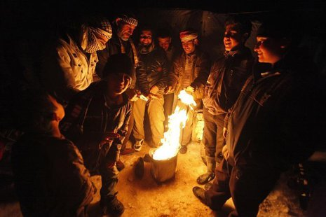 Syrian refugees from the town of Qara gather around a fire to keep themselves warm in a Syrian refugee camp on the Lebanese border town of A