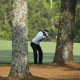 U.S. golfer Bubba Watson hits a shot from behind the trees on the 15th hole during the final round of the Masters golf tournament at the Aug