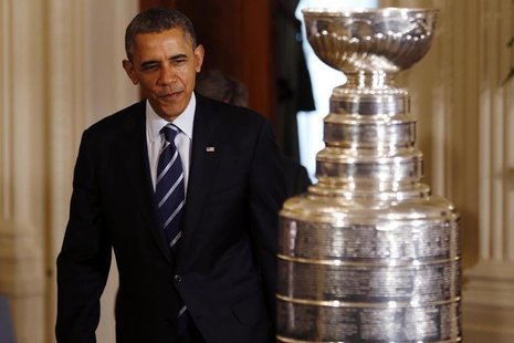 United States president Barack Obama enters the East Room behind the Stanley Cup prior to an event honoring the 2013 NHL Stanley Cup champio