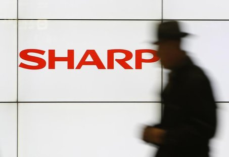 A pedestrian walks past a logo of Sharp Corp at a train station in Tokyo February 3, 2014. REUTERS/Yuya Shino