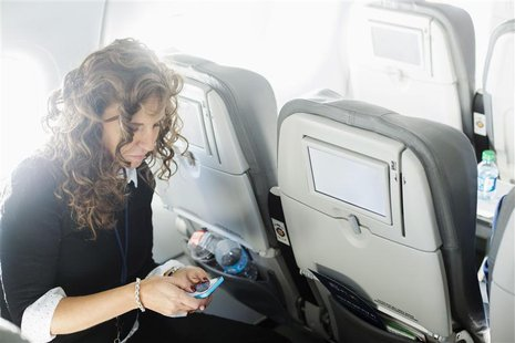 A woman uses her mobile phone to test a new high speed inflight Internet service named Fli-Fi while on a special JetBlue media flight out of