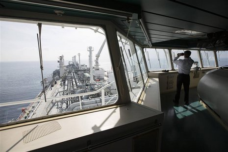 An officer uses binoculars as he stands on a tanker carrying liquefied natural gas in the Mediterranean, some 10 km (6 miles) from the coast