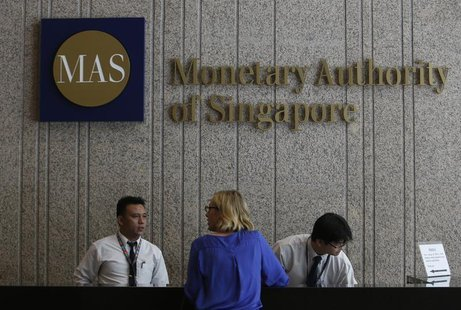 A visitor speaks to security officers at the building of the Monetary Authority of Singapore (MAS) in Singapore February 21, 2013. REUTERS/E