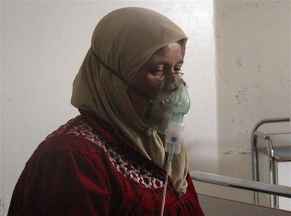A woman, affected by what activists say was a gas attack, breathes through an oxygen mask inside a field hospital in Kfar Zeita village in t