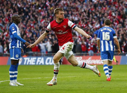 Arsenal's Per Mertesacker celebrates his goal against Wigan Athletic during their English FA Cup semi-final soccer match at Wembley Stadium