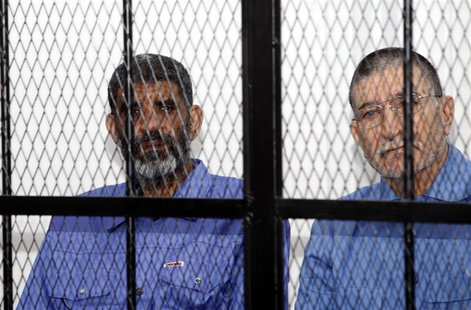 Abdullah al-Senussi (L), ex-spy chief in Muammar Gaddafi's government and Buzeid Dorda, ex-intelligence chief, sit behind bars during a hear