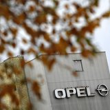 Leaves of a tree are pictured in front of a factory building with a logo of German car manufacturer Opel at the headquarters in Ruesselsheim