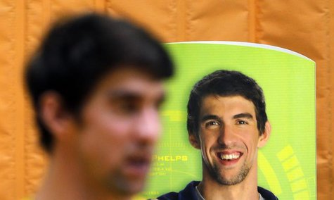 U.S. swimmer Michael Phelps stands next to a banner with his image during a promotional event in Sao Paulo December 4, 2013. REUTERS/Paulo W