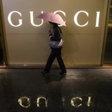 A woman holding an umbrella walks past a company logo of a Gucci boutique outside a shopping mall amid rainfall in central Guangzhou, Guangd