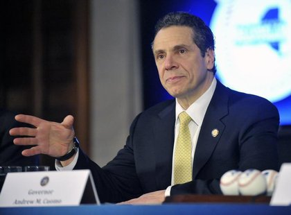 New York Governor Andrew Cuomo talks with reporters before signing the 2014-15 state budget at the State Capitol in Albany, New York, April